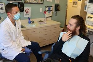 Dentist talking with patient in chair
